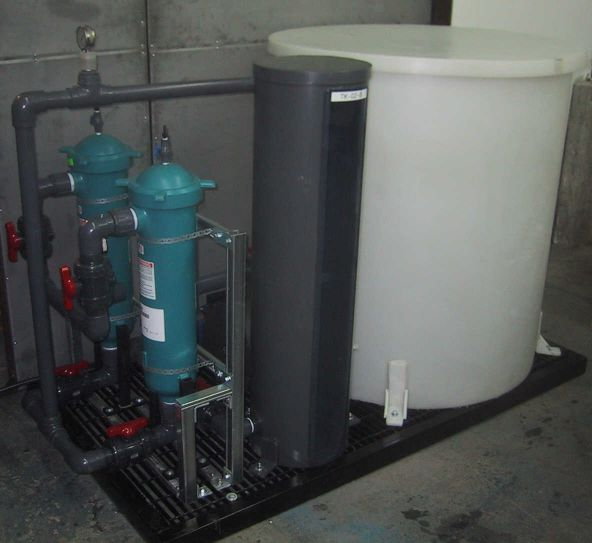 Skid mounted SX pilot plant feed delivery system with an SX feed tank, immersion heater, SX feed pump, filtration unit, and a calibration tube.